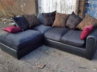 Fabulous black fabric corner sofa with lovely cushions. Brand New in the Box. can deliver