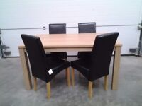 New dining table and 4 black faux leather chairs. Less 1/2 shop price Boxed Can deliver.