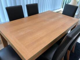 Oak effect table and 6 faux leather chairs