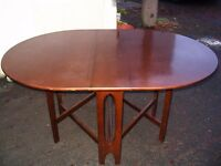 Oval drop leaf dining table with hinged flaps, solid wood kitchen table, to seat 4 people.