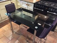 Black glass dining table and chairs for 2 people.
