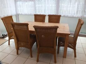 A pine table and six rattan wickerwork chairs