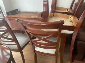Clean real wood dinning table in brown colour with chairs.