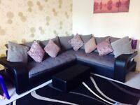 Large grey corner sofa with chrome detail on either side and footstool. Extra cushions included