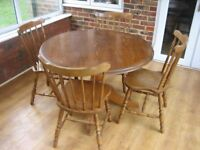 Round pine/oak table with four good chairs.