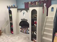 Boys Castle bunk bed, great condition, steps up and slide down, storage shelves in & on turrets