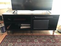 Dark brown wooden TV Unit with shelved and metal feet.