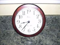 A wall mounted wood surround clock.