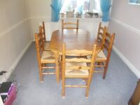 Dining table and 6 chairs in good condition strong pine with wicker seats