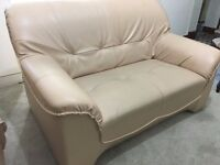 Beige faux-leather two seater sofa. Very comfortable., good condition