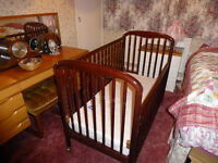 Dark brown wooden cot. Has dropped down side. Included mattress if wanted.