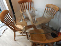 Round Glass table top 42 Inches across, with wooden legs, 3 x Spindel Chairs, 1 X Captains Chaira.