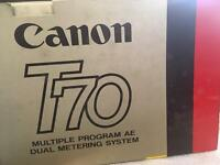 Vintage Canon T70 camera with accessories