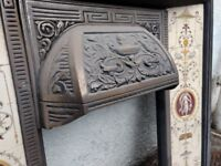 Traditional fireplace surround, metal with tiled side panels.