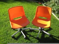 Two IKEA orange plastic swivel chairs