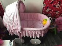 Pink wicker crib on moving wheels