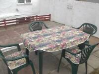 Green plastic table and chairs, plus chair cover, cushions and tablecloth