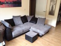 Black and grey corner sofa with footstall
