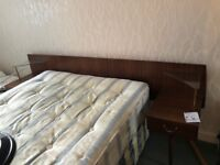 Vintage wooden headboard with bedside tables