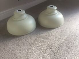 A pair of industrial looking light shades in cream