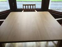 Attractive solid wood kitchen table with sturdy fashionable chairs with red seats.