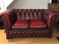 An oxblood red leather two seater Chesterfield sofa