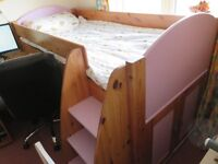 Stompa Childrens high bed with storage shelves and table.
