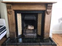 A Victorian style fireplace and surround wood mantle and tiles.