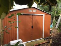 Metal two door shed, 10 feet by 7.6. Approximately 7 feet at tallest point.