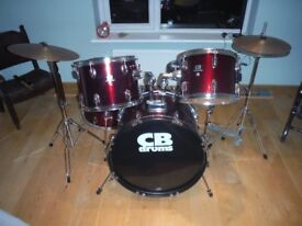 Beautiful metalic red drum kit with drum sticks and stool
