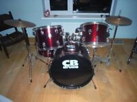 Beautiful metalic red drum kit with drum sticks and stool