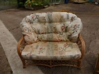 Conservatory furniture for sale. 1 double settee, 1 single chair and 1 stool. Cane with cusions