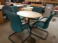 Round meeting table and four green chairs
