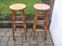 Two tall pine four legged kitchen stools.