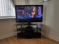 Samsung LCD TV with black glass stand and samsung blue ray player and surround system.