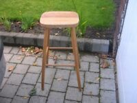 A tall four legged stool with rectangular seat.