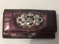 Kathy Von Zealand purple purse with badge logo on the front.