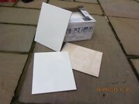 Unused boxes of White glazed wall tiles for sale.