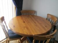 extendable wooden round dining table and four chairs good condition