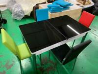 Brand new extendable dining table covered by black glass on top