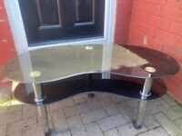 Glass coffee table oval shaped black effect with wheels on legs in good condition