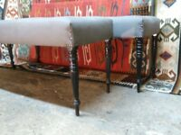 Pair of long upholstered benches made on antique ebonised legs from the aesthetic period tufted tops