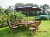 Quality hardwood picnic table (extends to 8 ft) with 8 folding chairs and parasol.