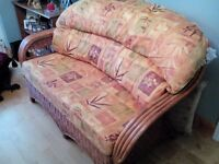Conservatory 2 seater settee in antique polished pine with orange patterned back and seat cushions