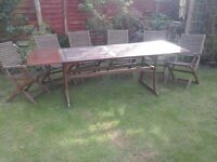 Wooden garden table and six chairs.