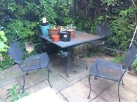Sold heavy metal garden table and four chairs.