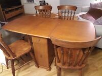 Drop leaf table with 2 drawers and 2 cupboards. 4 solid chairs .can be sold seperate
