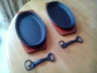Pair of cast iron sizzle plates with wood bases
