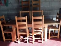 Solid oak extending table and six chairs.