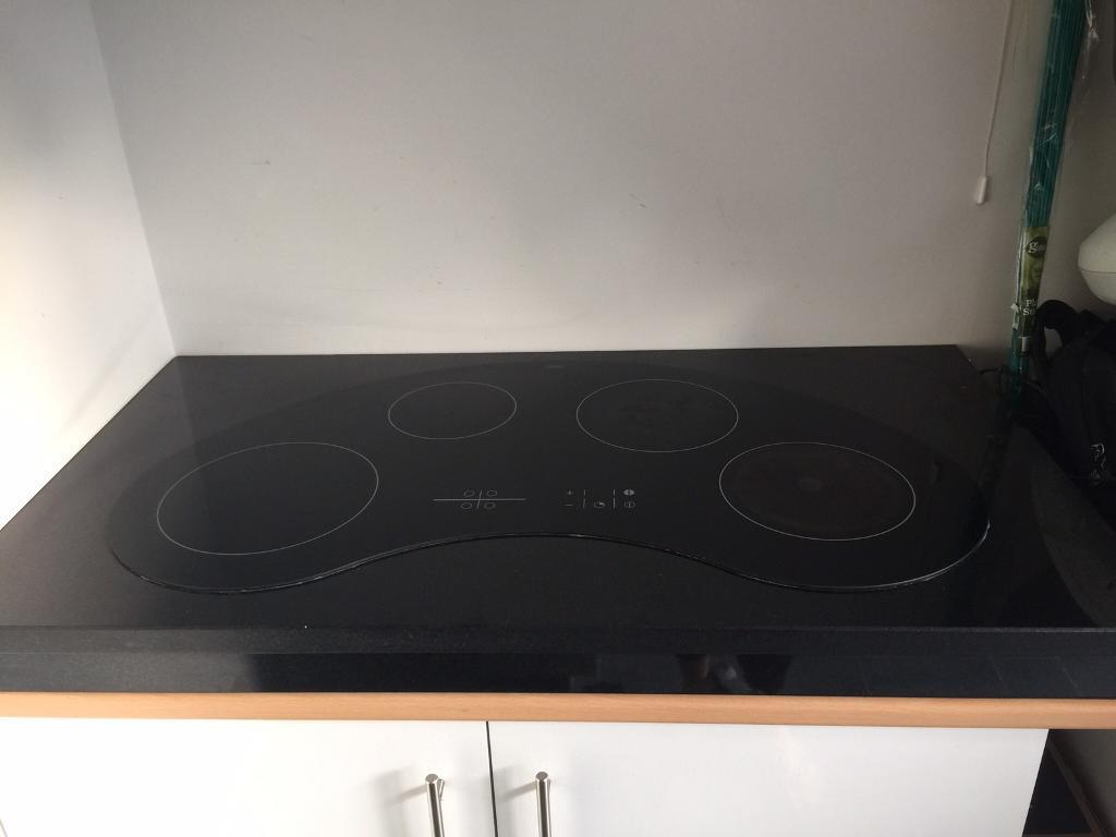 Kidney shaped electric touch screen hob fitted in black granite